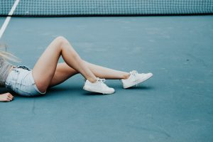 Pair of female legs on tennis court