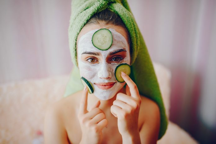 Girl with face mask and pieces of cucumber