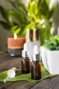 Serum on the table with plants and candle on the background