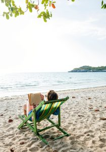 Woman lying on the beach, reading and taking sunbathe