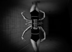 Black and white photo of a woman's body in a pool