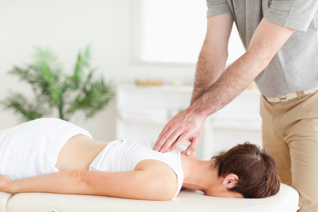 A masseur is massaging a female customer's back