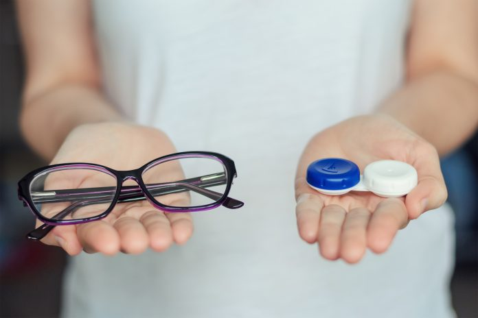 Woman holding eyeglasses and eye contacts