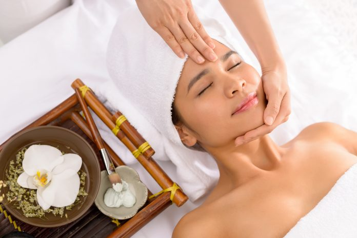 Spa therapist preparing skin of the client for the facial mask