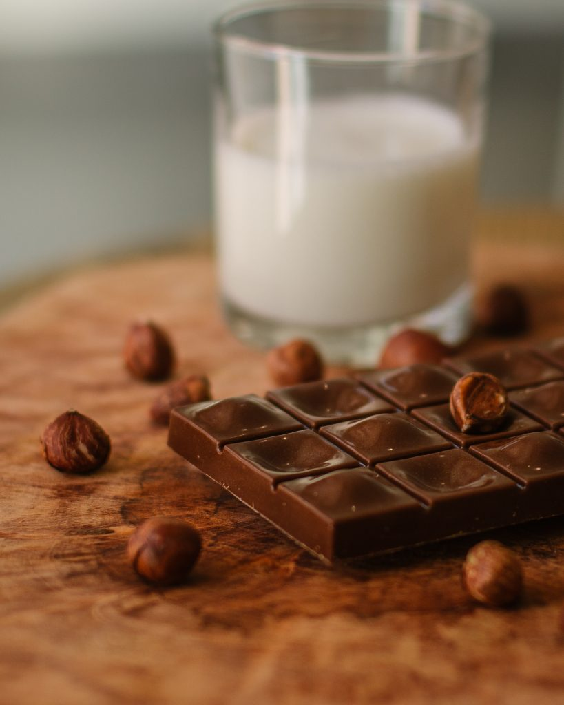 Dark chocolate with a glass of milk behind