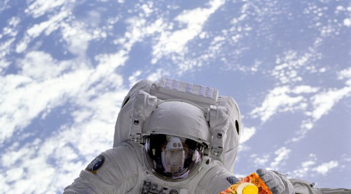 The astronaut in the space with a piece of pizza in his hand