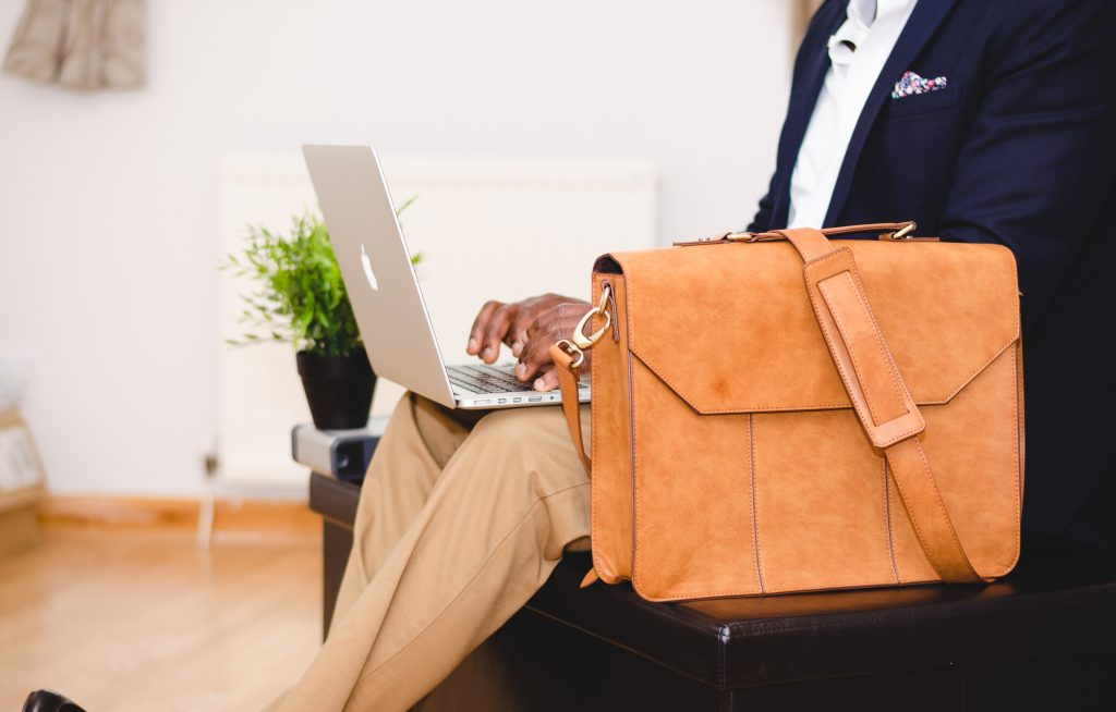 Man sitting on a chair with brown bag and a laptop