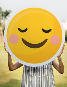 A woman holding huge emoji
