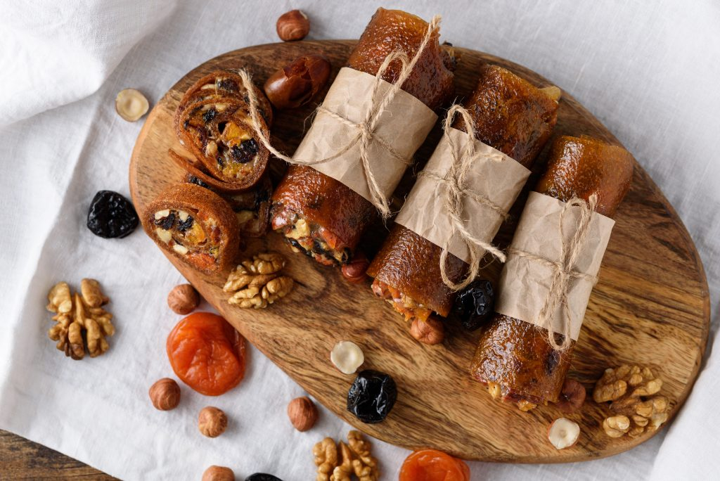 fruit pastille with dried fruits, nuts and honey wrapped in parchment paper, healthy dessert, vegetarian snack concept, healthy food, harmeless dessert made of apples, home-made sweets.